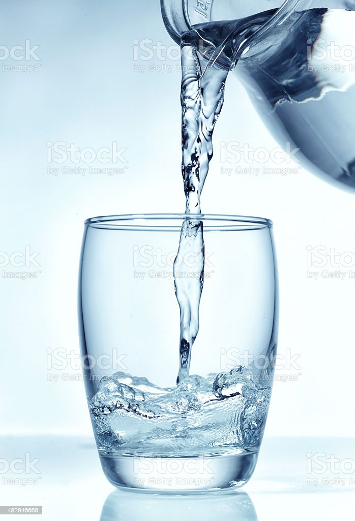 fresh water pouring into glass stock photo