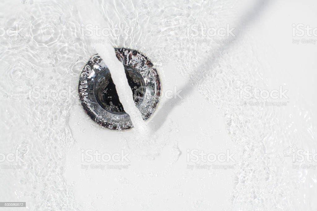 Fresh water running down the drain stock photo
