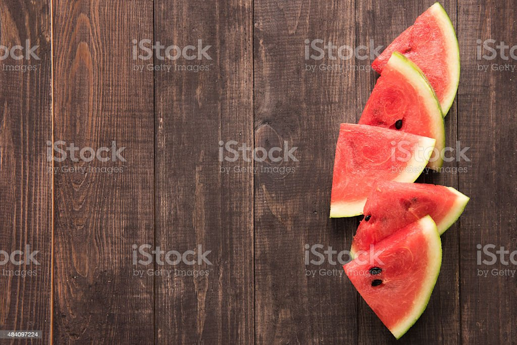 Fresh watermelon pieces placed on wooden background. stock photo