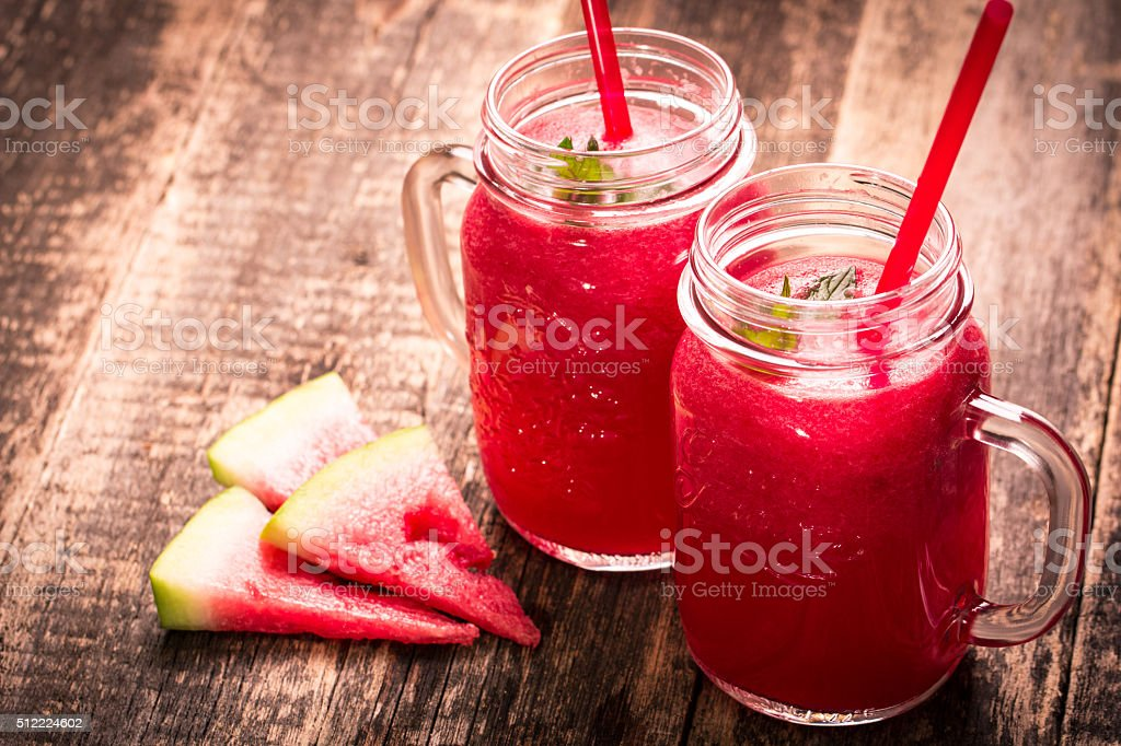Fresh watermelon smoothie drink in mason jar on black stone. stock photo