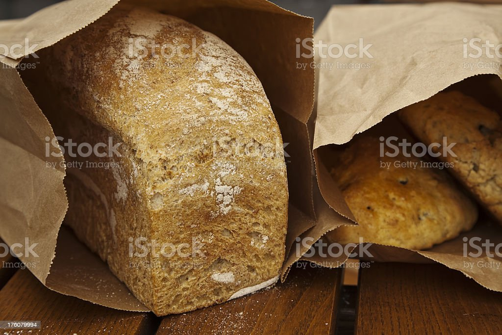 Fresh wheat breads and pastries in brown paper bags. royalty-free stock photo