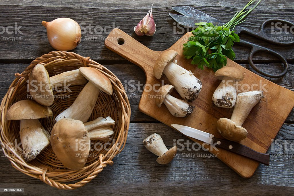 Fresh white mushrooms in basket on a rustic wooden board. stock photo