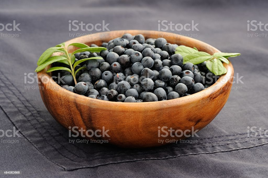 Fresh wild blueberries with green leaves in handmade wooden bowl stock photo
