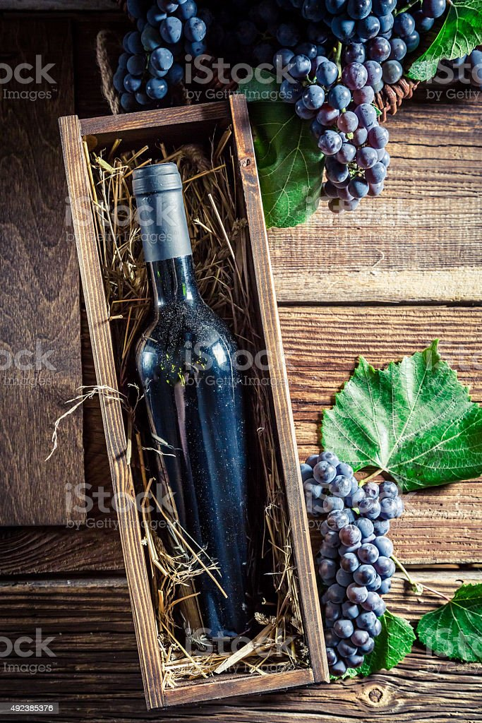 Fresh wine in bottle in old wooden box stock photo