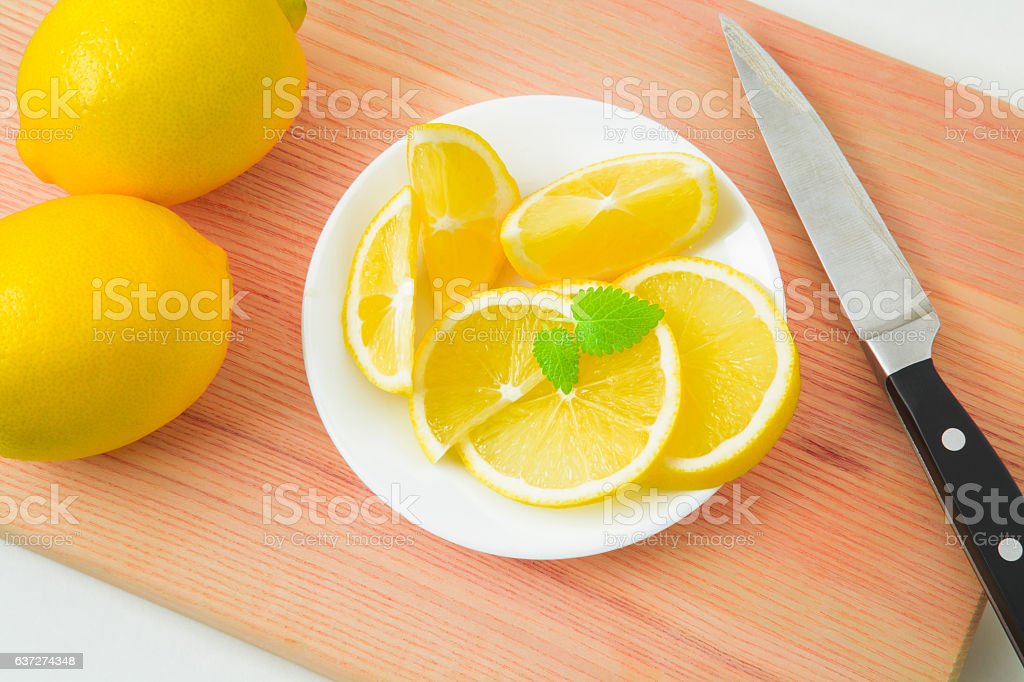 Fresh, yellow lemons in the dish on the wooden board. stock photo