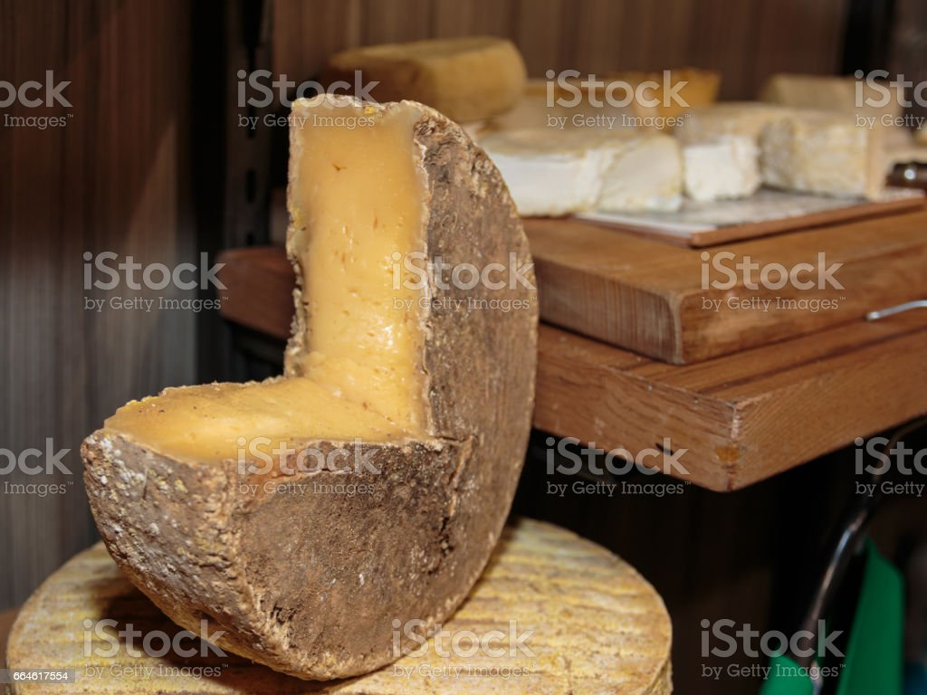 Fresh Yellow Rounded Cheese and Assortment of Cheese in background stock photo