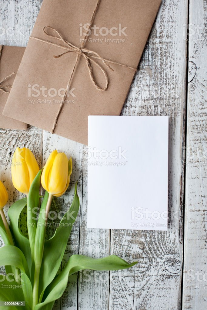 Fresh yellow tulips and empty tag on teal painted wooden background. Selective focus. Place for text. Square image stock photo