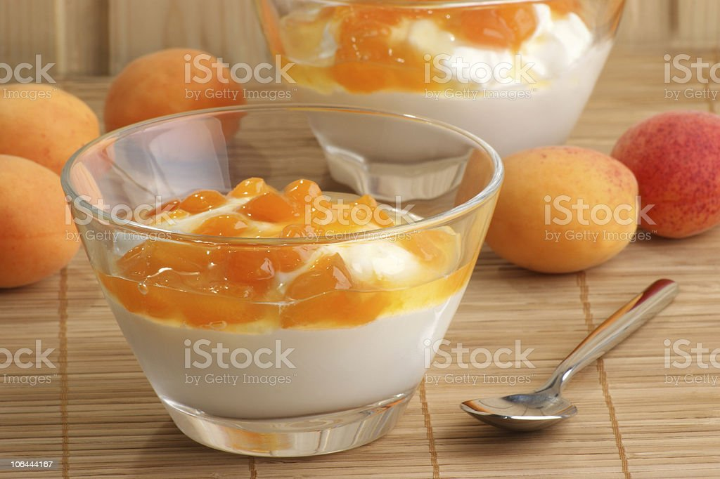 Fresh yoghurt in a glass bowl topped with apricot compote stock photo