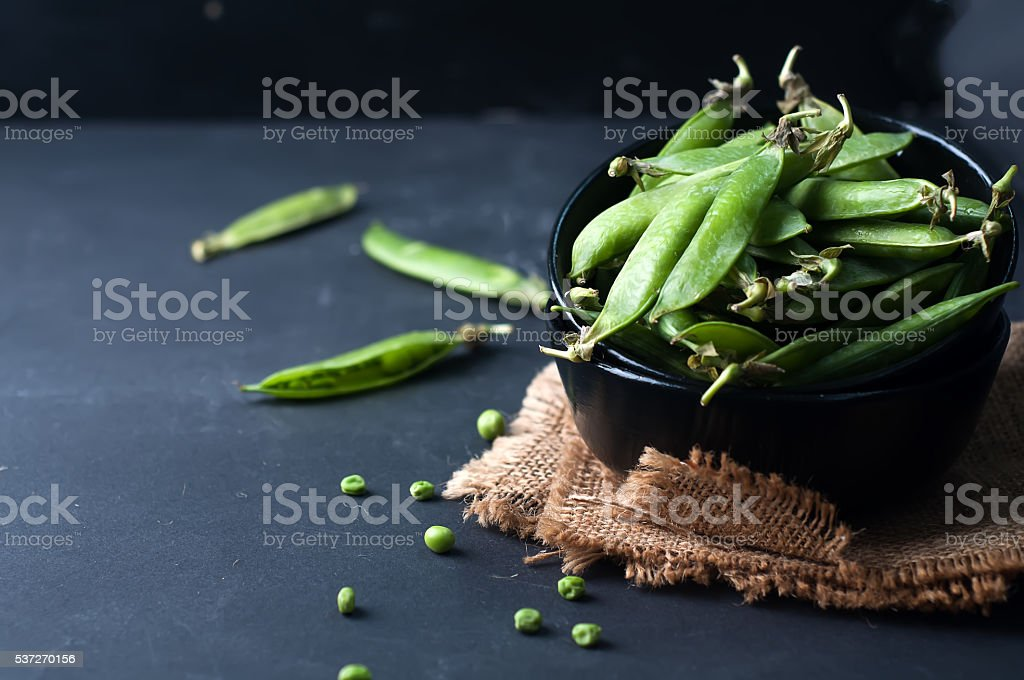 Fresh, young, unpeeled green peas stock photo