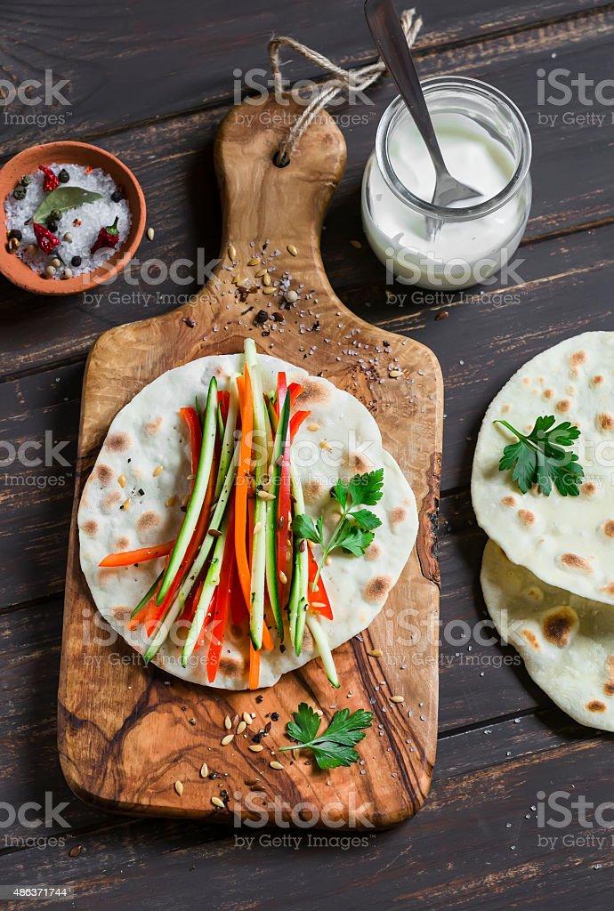 fresh zucchini, carrots, pepper, natural yogurt and a homemade tortilla stock photo
