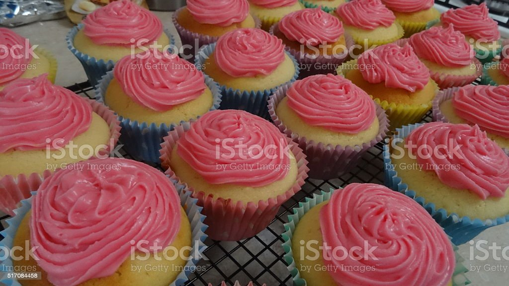 Freshly baked and iced cupcakes stock photo