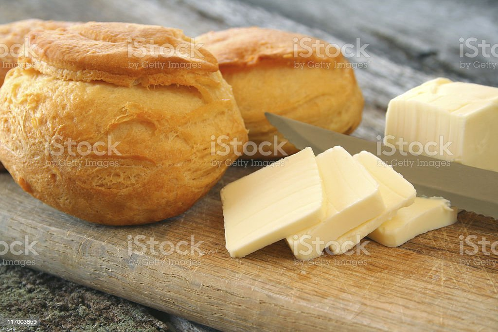Freshly baked biscuits with butter and knife on wood board stock photo