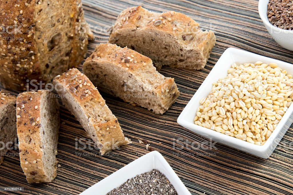 Freshly baked bread chopped up next to some grains stock photo