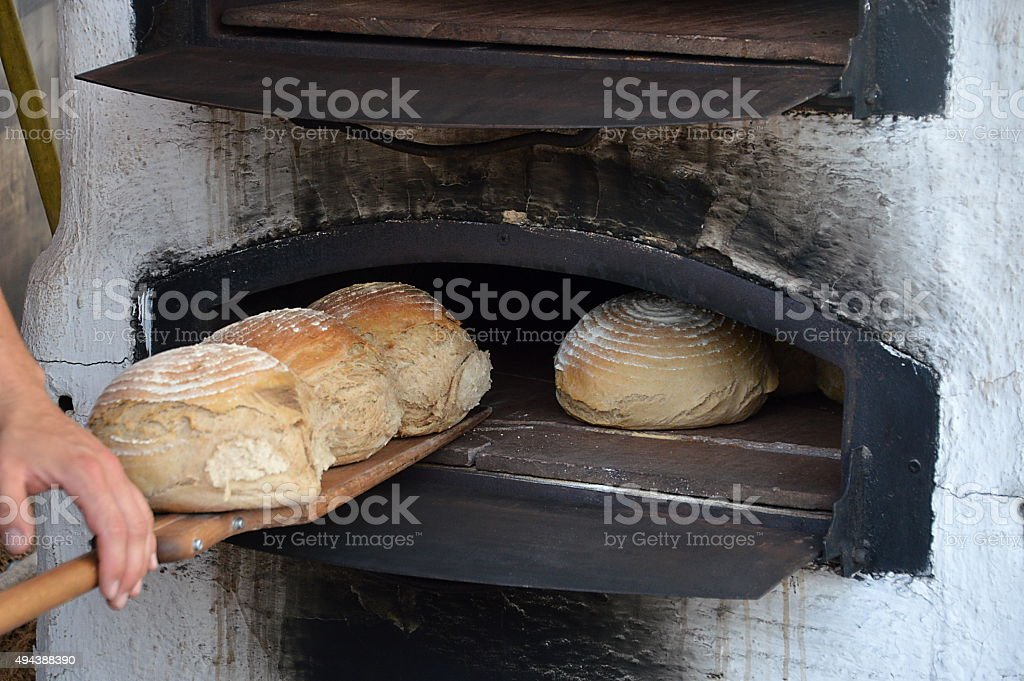 freshly baked bread in old timey wood oven stock photo
