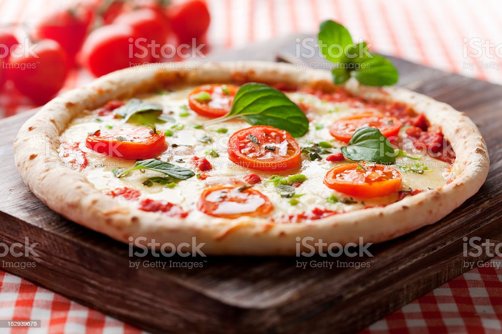 Freshly baked cheese and tomato pizza on wooden slab royalty-free stock photo