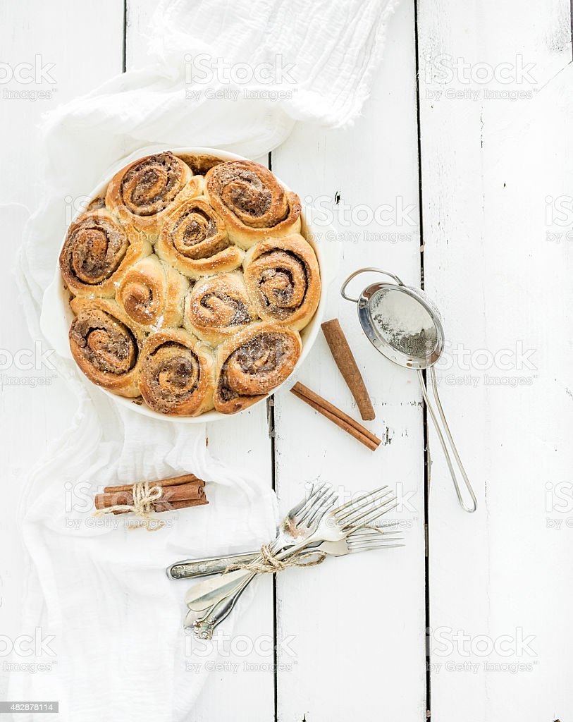 Freshly baked cinnamon buns in dish on a rustic wooden stock photo