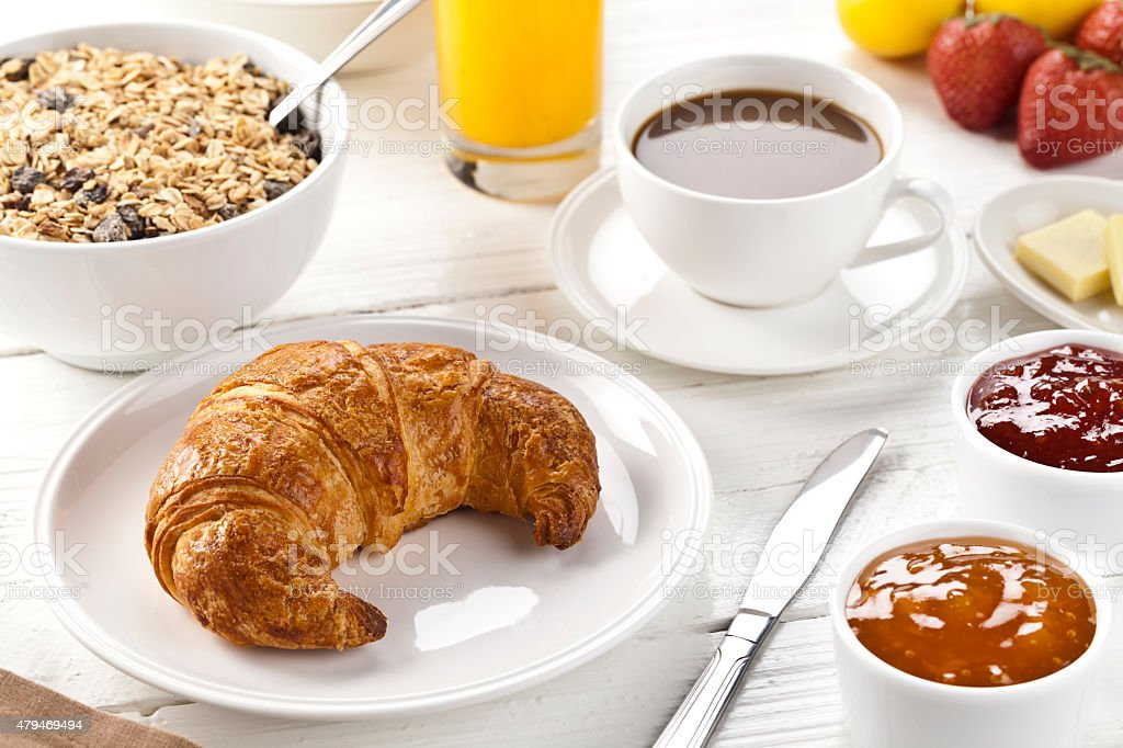Freshly baked croissant served on a withe rustic dinning table. stock photo