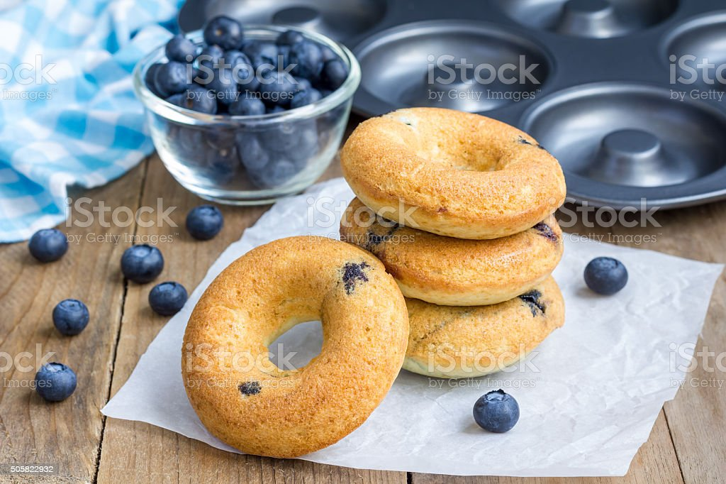 Freshly baked doughnuts with blueberries for breakfast stock photo
