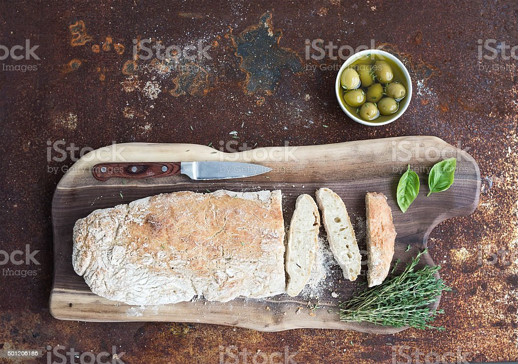 Freshly baked homemade ciabatta bread with olives, basil and thyme stock photo