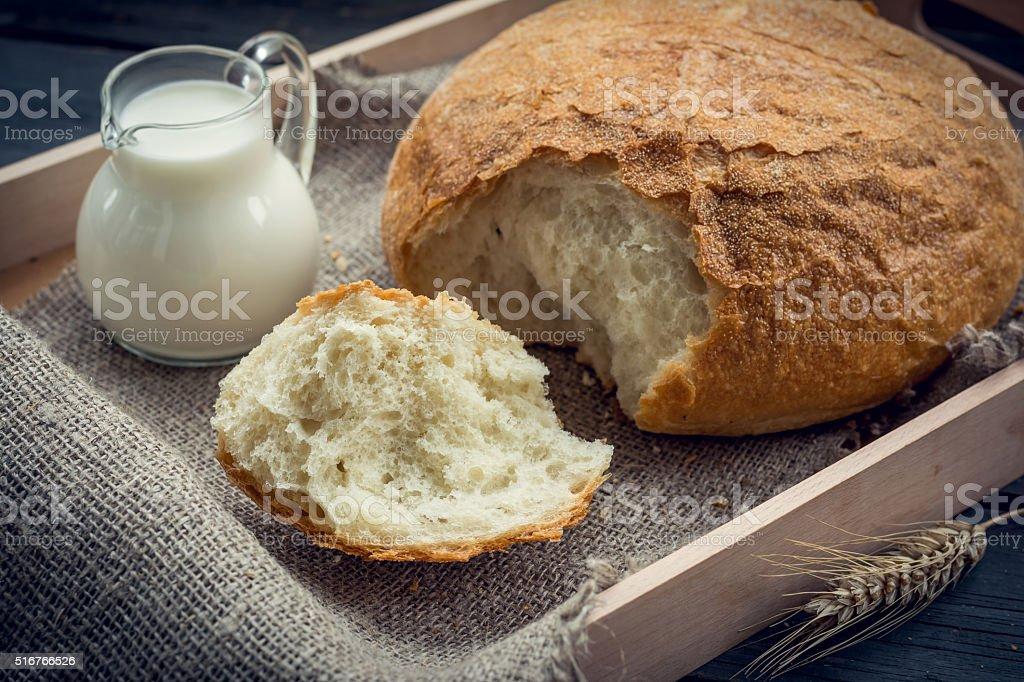 Freshly baked multi-grain bread with jug of milk stock photo