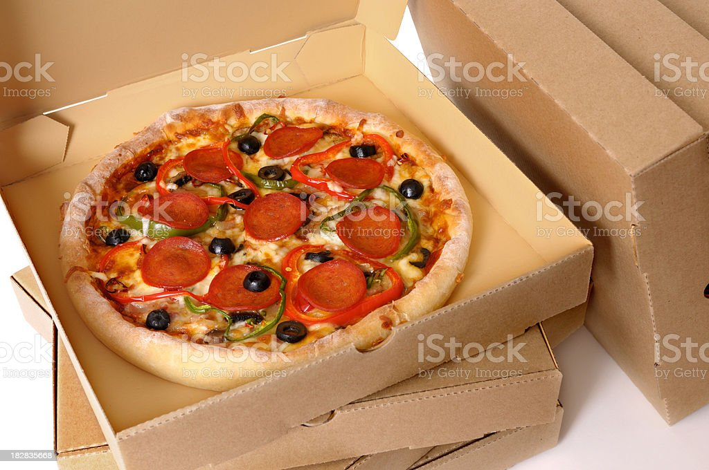 Freshly baked Pizza with stack of delivery boxes royalty-free stock photo