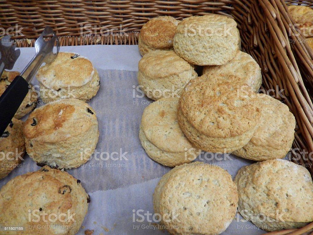 Freshly baked savoury cheese scones / sweet raisin scones, wicker basket stock photo