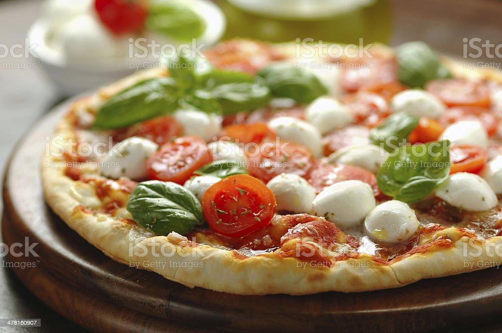 Freshly baked tomato and mozzarella pizza stock photo