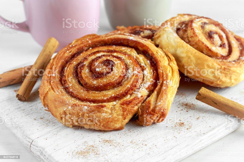 Freshly Baked Traditional Sweet Cinnamon Rolls, Swirl on white wooden board stock photo