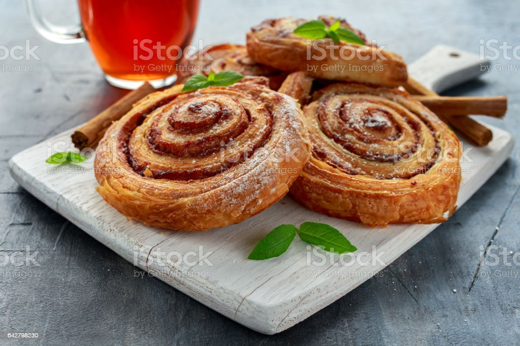 Freshly Baked Traditional Sweet Cinnamon Rolls, Swirl on white wooden board with hot black Tea and mint stock photo