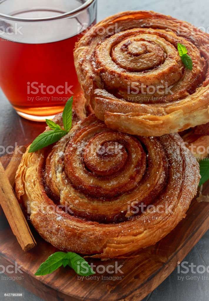 Freshly Baked Traditional Sweet Cinnamon Rolls, Swirl with hot black Tea and mint stock photo