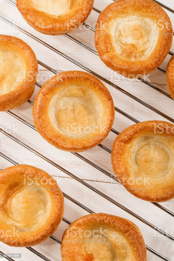 freshly baked yorkshire pudding on a cooling rack stock photo