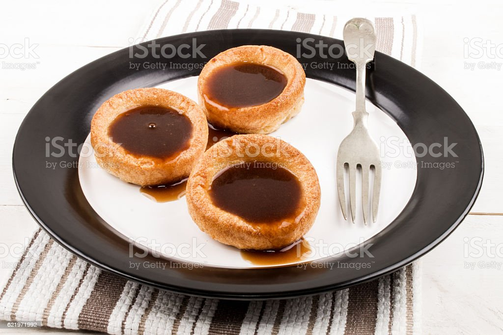 freshly baked yorkshire pudding with gravy on a plate stock photo