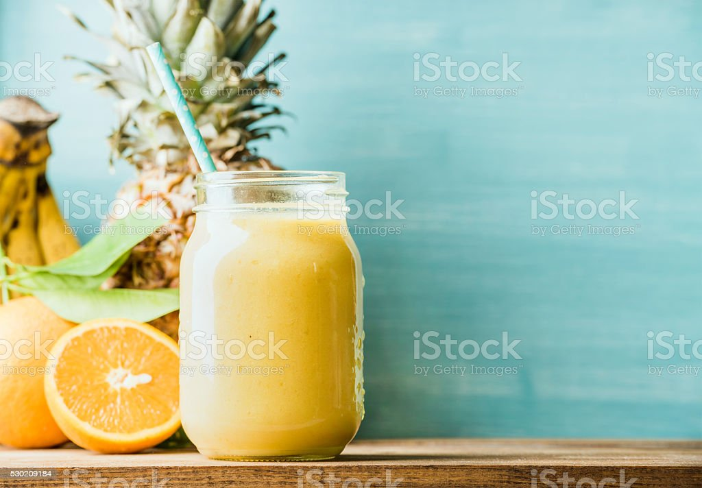 Freshly blended yellow and orange fruit smoothie in glass jar stock photo