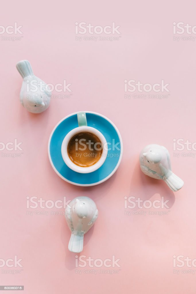 Freshly brewed morning cup of espresso coffee with a beautiful crema on the pink background with green ceramic birds decorating the flat lay stock photo