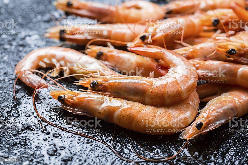 Freshly caught shrimp on black rock stock photo