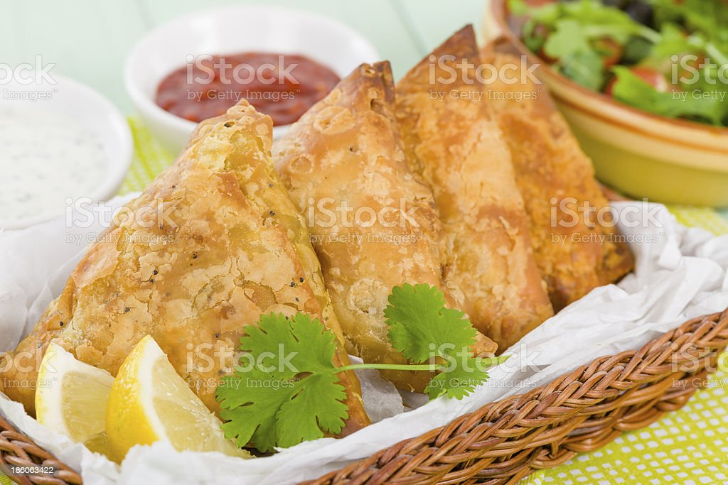 4 freshly cooked samosas in a tray with dips royalty-free stock photo