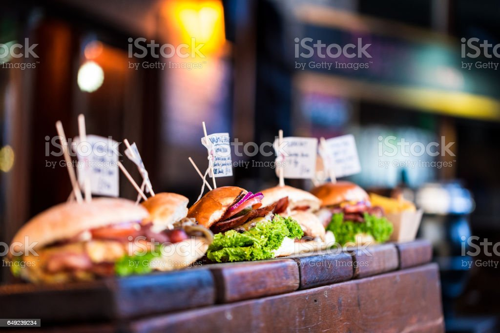 Freshly flame grilled burgers displayed in a row stock photo