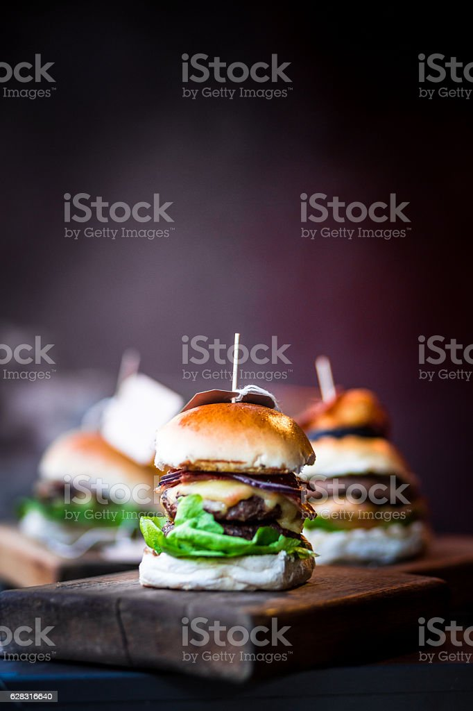 Freshly flame grilled burgers in a row on wooden board stock photo