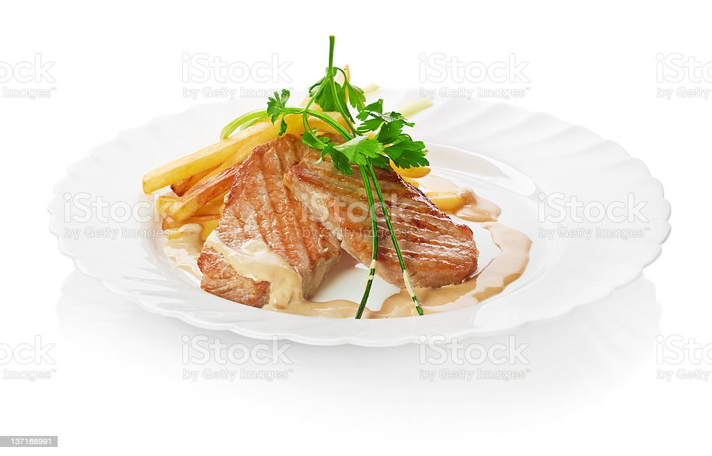 Freshly grilled steak with French Fries, parsley and tomatoes royalty-free stock photo
