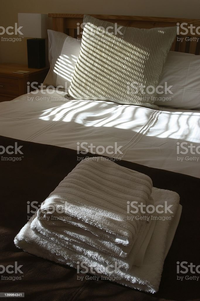 Freshly made bed in a smart hotel room royalty-free stock photo