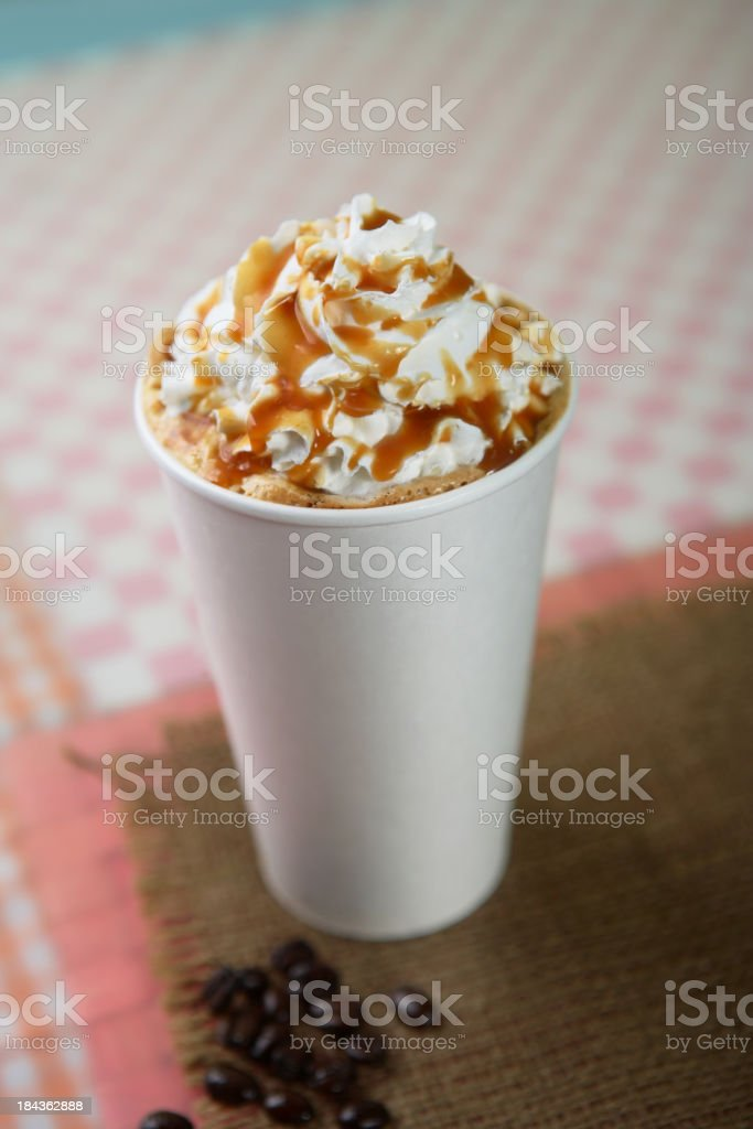 A freshly made latte with caramel sauce drizzled over cream stock photo