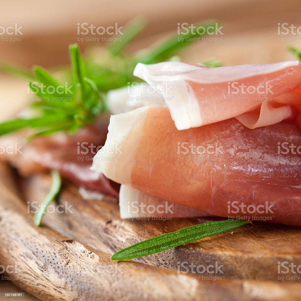 Freshly made Prosciutto Crudo on a wooden plate stock photo