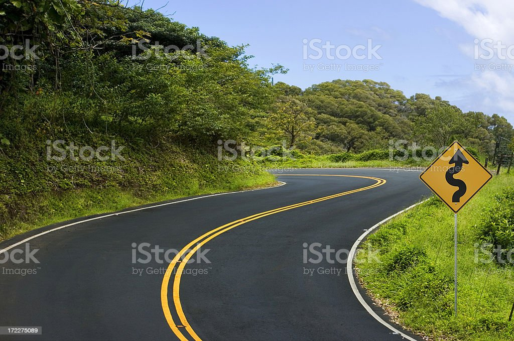 Freshly paved and winding road disappears around the turn stock photo