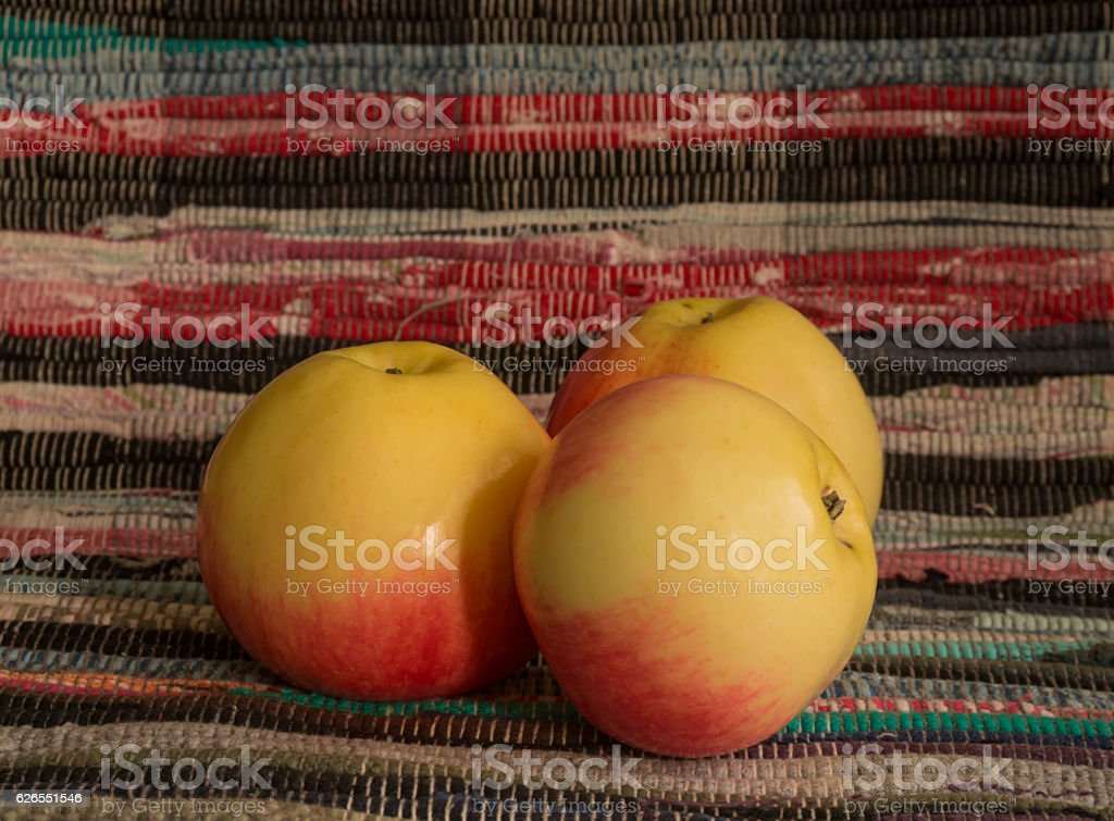 Freshly picked apples and motley homespun fabric stock photo