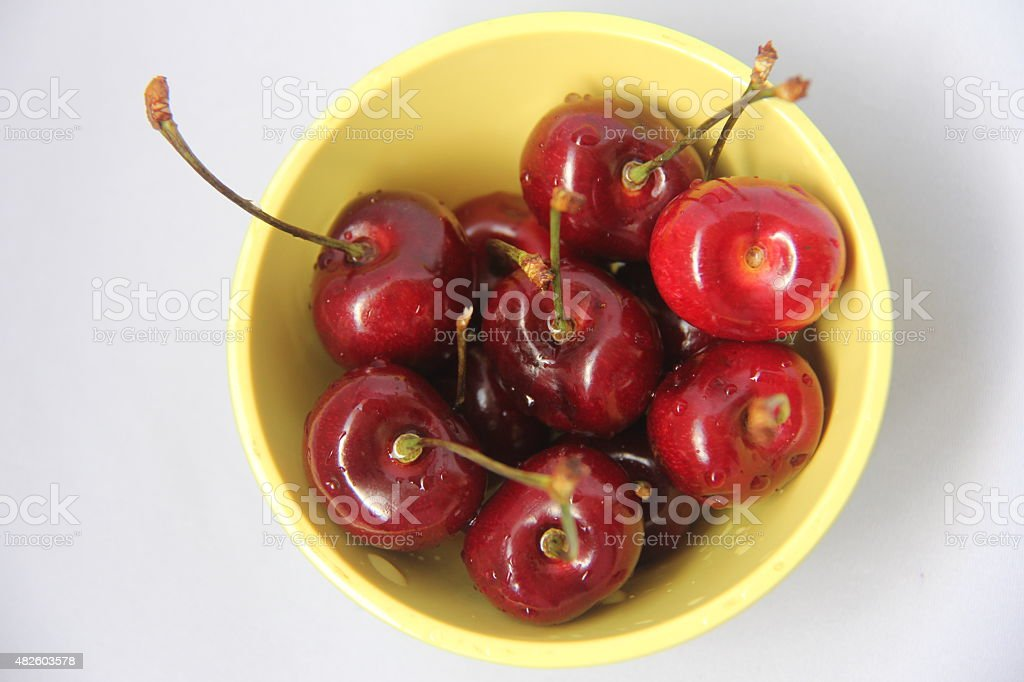 Freshly picked cherries in a yellow bowl stock photo