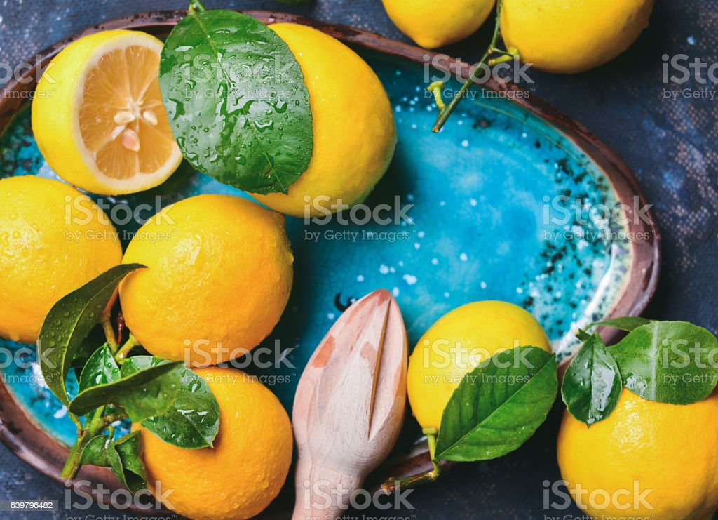 Freshly picked lemons with leaves and pounder in blue plate stock photo
