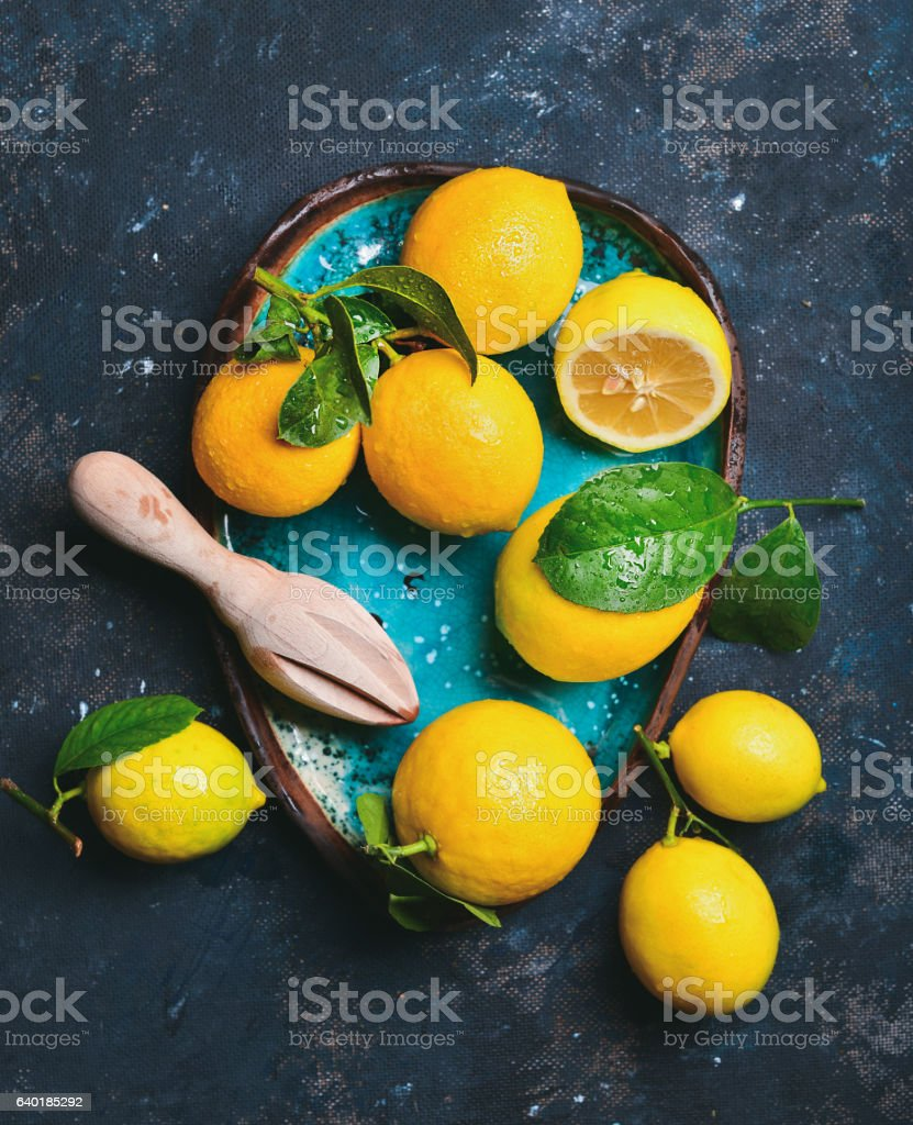 Freshly picked lemons with leaves in blue ceramic plate stock photo