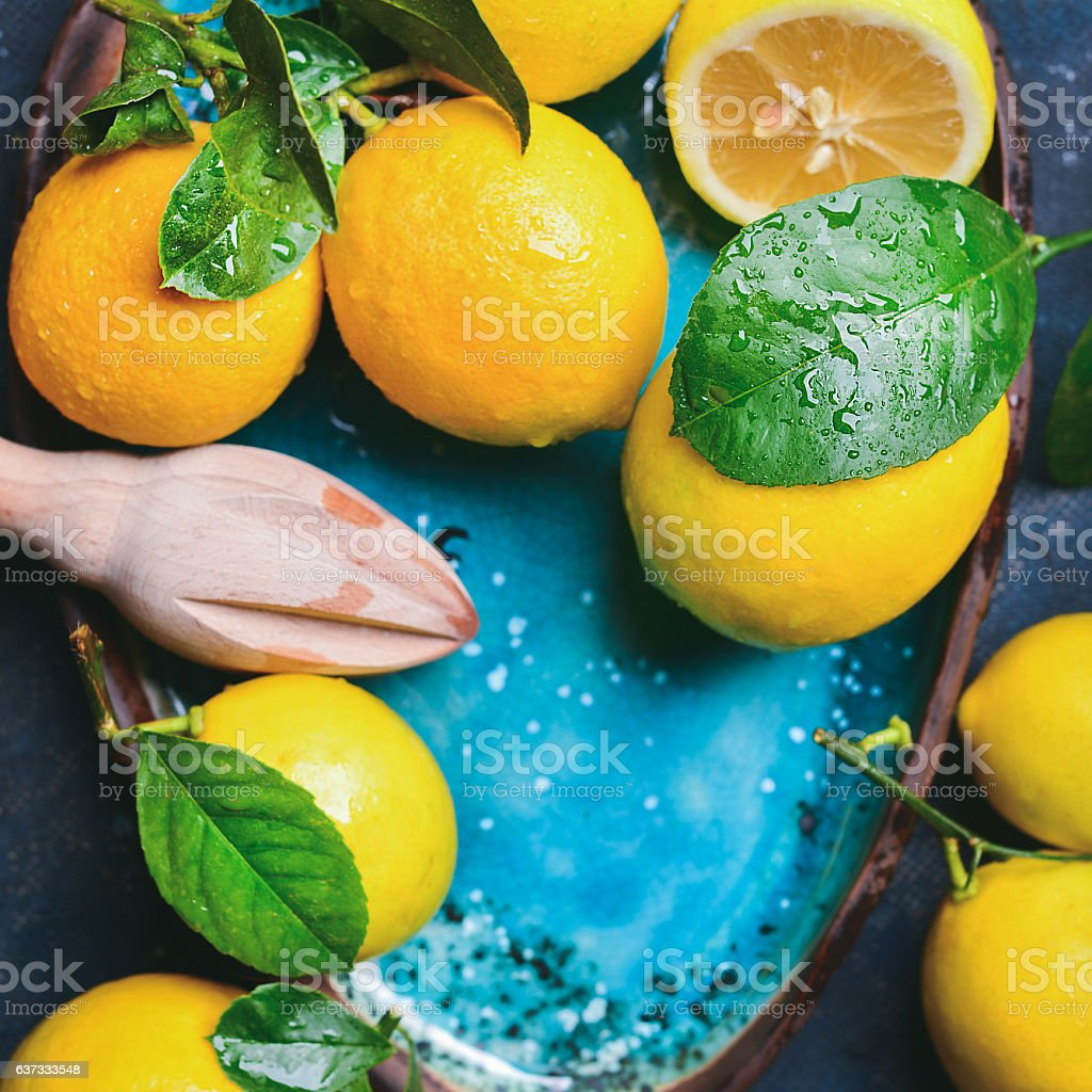 Freshly picked lemons with leaves in blue plate, copy space stock photo