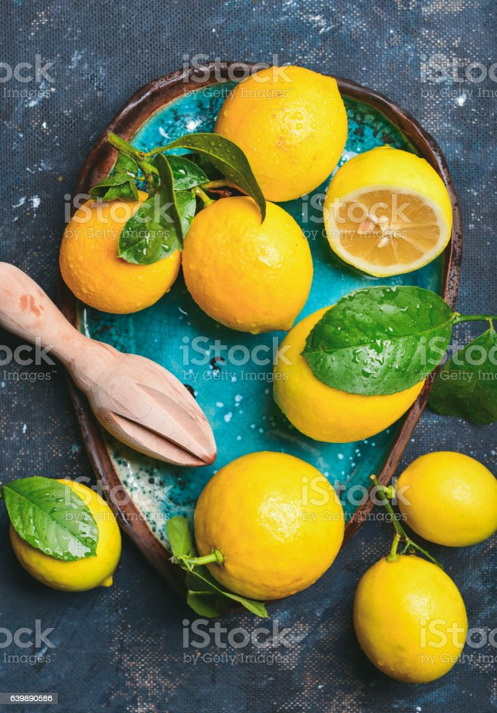Freshly picked lemons with leaves in bright blue ceramic plate stock photo
