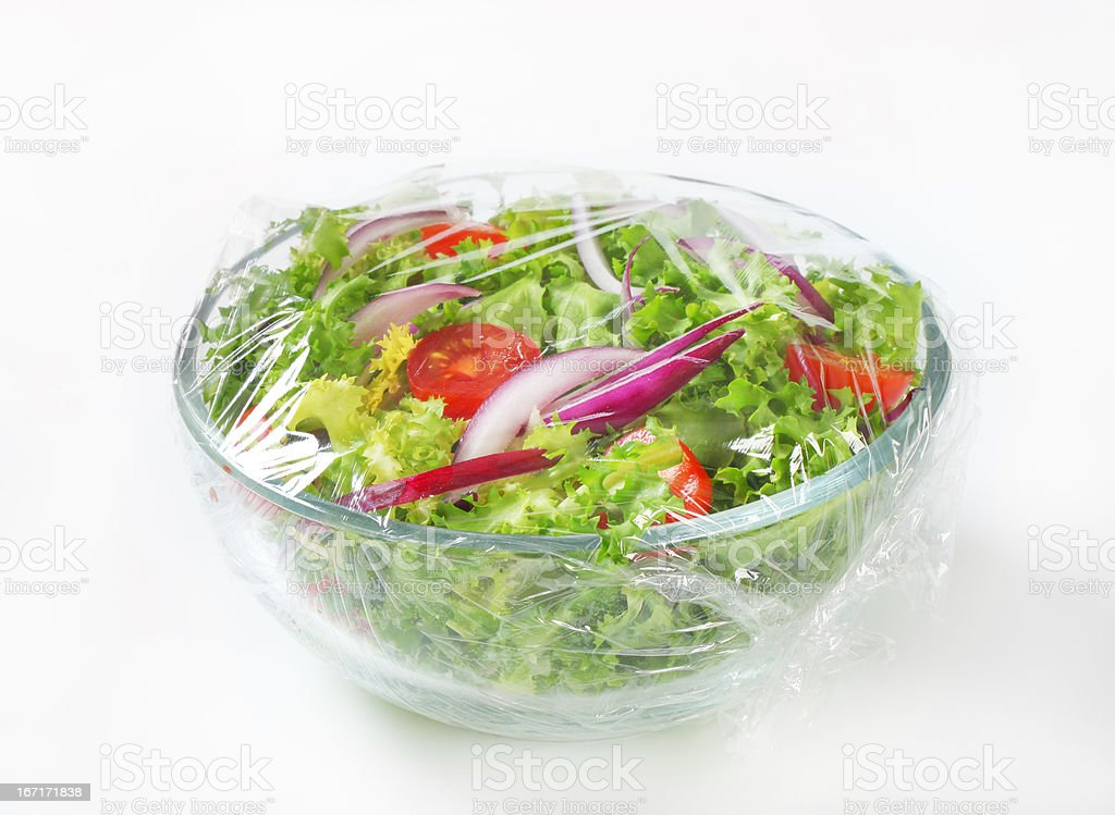 Freshly prepared vegetable salad covered in plastic wrap stock photo
